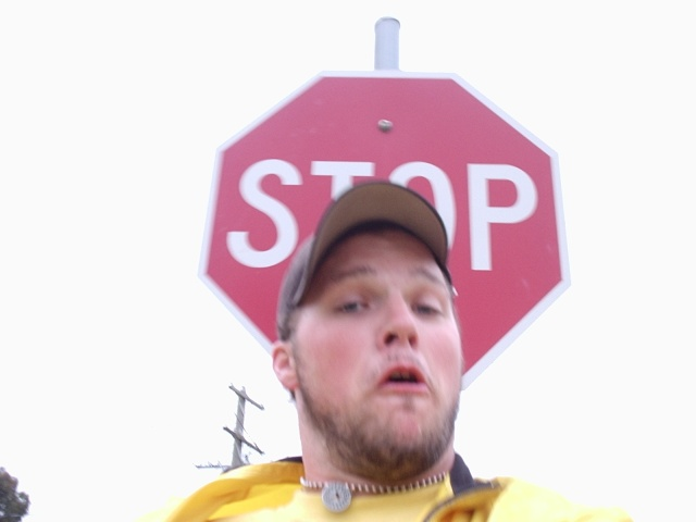 Jeff jumping in front of a stop sign